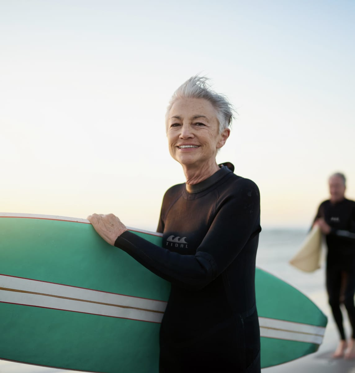 older woman holding surfboard on beach